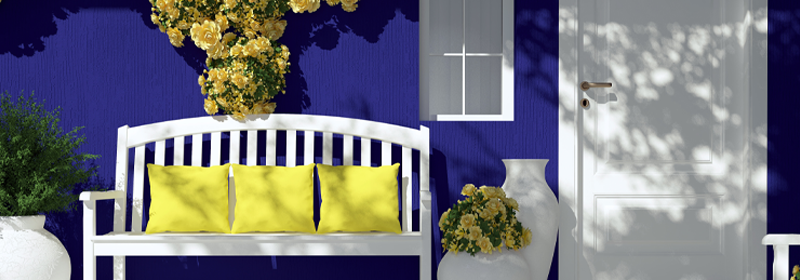 Porch of blue house with white bench and yellow flowers