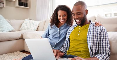 Couple at home in living room looking at options together on a a laptop