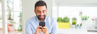 Smiling man at home looking at loan options on smartphone
